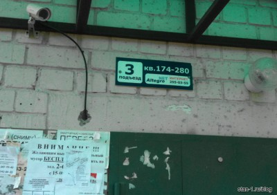 Табличка с номерами квартир и рекламой ШПД над подъездом дома в Воронеже
